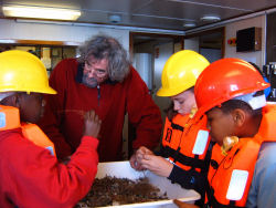 Dr. Dave McGrath and students from the Claddagh National School examining samples of marine life aboard the RV Celtic Voyager