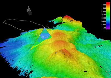 Image of a 3D animation of the largest feature mapped in the Charlie-Gibbs Fracture Zone, extending 3708m above the surrounding seabed. The shallowest depth is 979m below sea surface, with depths of 4687m recorded at the base some 20km away.  Note the legend is depth rather than height. The triangle is a single slice (swathe) of multibeam data acquired from the ship on the sea surface, moving along its survey track – the white line.