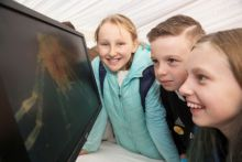 Students looking at crustacean larva on the screen at the Marine Institutes exhibit held at CuanBeo event in Clarenbridge. Photo courtesy of Andrew Downes, Xposure.